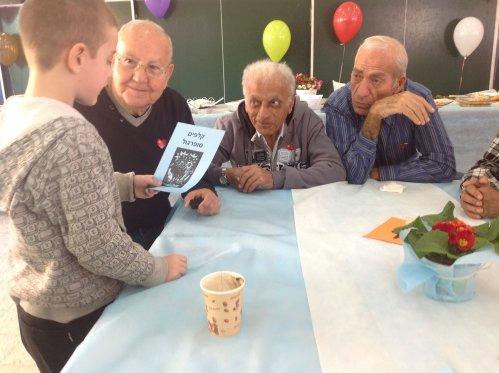 """מסביב לשולחן – פעילות בין דורית. מימין לשמאל: יצחק אשכנזי, אשר איש שלום, שלמה סבח ותלמיד מביה""""ס"""